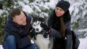 Familia hermosa, un hombre y una muchacha en bosque del invierno con el perro Juego con el husky siberiano del perro almacen de video