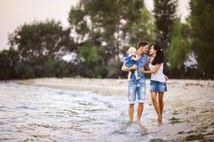 Familia hermosa y elegante vestida joven de mamá, de papá y de hija de la gente del tres de un año en los hombros de un hombre a  fotos de archivo