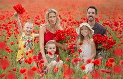 Familia hermosa y feliz junto, en un campo rojo de amapolas Fotos de archivo