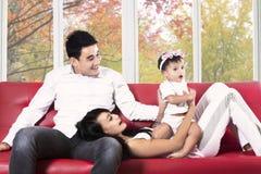 Familia hispánica alegre en el sofá Imágenes de archivo libres de regalías
