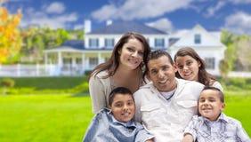 Familia hispánica atractiva delante de su nuevo hogar Imágenes de archivo libres de regalías