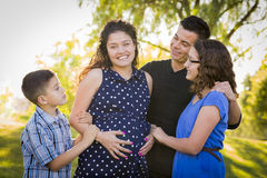 Familia hispánica atractiva feliz con su madre embarazada Outd Imagen de archivo