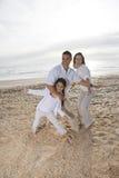 Familia hispánica con la muchacha que se divierte en la playa imágenes de archivo libres de regalías