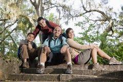 Familia hispánica con los morrales que van de excursión en parque Imagenes de archivo