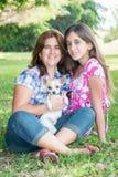 Familia hispánica con su pequeño perro en un parque Foto de archivo libre de regalías