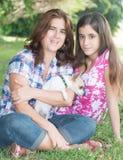 Familia hispánica con su pequeño perro en un parque Imagen de archivo libre de regalías