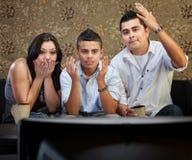 Familia hispánica dada una sacudida eléctrica que ve la TV Foto de archivo libre de regalías