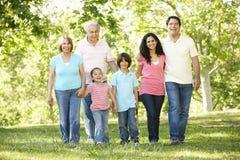 Familia hispánica de la generación multi que camina en parque Imagen de archivo
