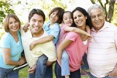 Familia hispánica de la generación multi que se coloca en parque Fotografía de archivo libre de regalías