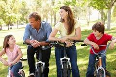 Familia hispánica en las bicis en parque Fotos de archivo libres de regalías
