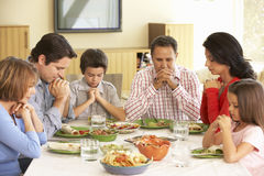 Familia hispánica extendida que dice rezos antes de comida en casa foto de archivo