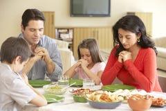 Familia hispánica joven que dice rezos antes de comida en casa Foto de archivo