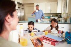 Familia hispánica que come el desayuno en casa antes de escuela Imagen de archivo