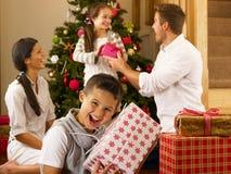 Familia hispánica que intercambia los regalos en la Navidad Imagen de archivo libre de regalías