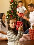 Familia hispánica que intercambia los regalos en la Navidad foto de archivo libre de regalías