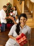Familia hispánica que intercambia los regalos en la Navidad Imagen de archivo