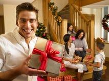 Familia hispánica que intercambia los regalos en la Navidad Foto de archivo
