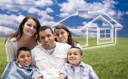 Familia hispánica que se sienta en campo de hierba con la casa de Ghosted detrás Foto de archivo libre de regalías