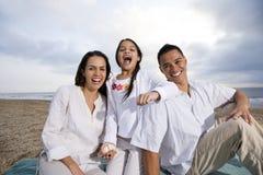 Familia hispánica que se sienta en la manta en la playa Fotografía de archivo