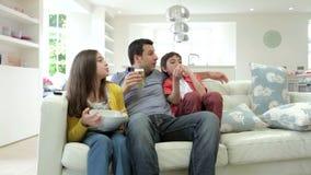 Familia hispánica que se sienta en Sofa Watching TV junto metrajes