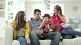 Familia hispánica que se sienta en Sofa Watching TV junto almacen de metraje de vídeo
