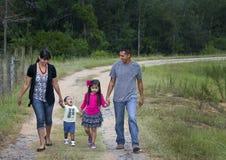 Familia hispánica - recorriendo en lluvia Fotos de archivo libres de regalías