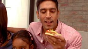 Familia hispánica sonriente que come la pizza en sala de estar metrajes