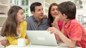 Familia hispánica usando el ordenador portátil en casa almacen de metraje de vídeo