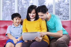 Familia hispánica usando la tableta en casa Fotos de archivo