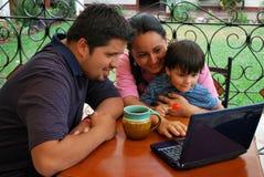 Familia hispánica usando un ordenador Fotografía de archivo libre de regalías