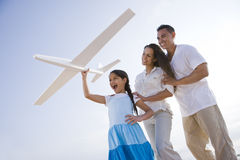 Familia hispánica y muchacha que se divierten con el plano del juguete Foto de archivo