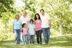 Familia hispánica de la generación multi que camina en parque Imagen de archivo libre de regalías