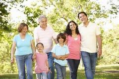 Familia hispánica de la generación multi que camina en parque Imágenes de archivo libres de regalías