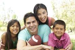Familia hispánica en parque con el balón de fútbol Imágenes de archivo libres de regalías