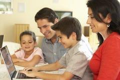 Familia hispánica joven usando el ordenador en casa Imagenes de archivo