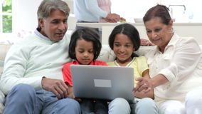 Familia india multigeneración con el ordenador portátil que se sienta en el sofá metrajes