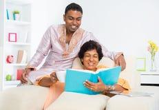 Familia india que lee un libro Imágenes de archivo libres de regalías
