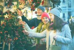 Familia interesada de tres en el mercado de la Navidad Fotografía de archivo libre de regalías