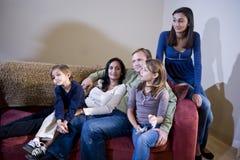 Familia interracial de cinco que se sientan junto imagen de archivo libre de regalías