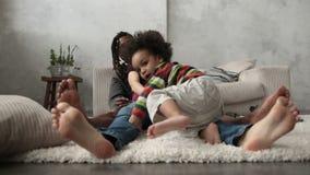 Familia interracial feliz que se sienta descalzo en piso almacen de video