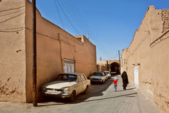 Familia iraní que camina más allá de las casas de la arcilla y de los coches retros Imágenes de archivo libres de regalías