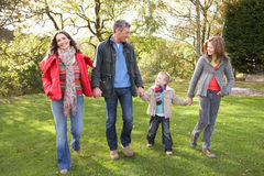 Familia joven al aire libre que recorre a través de parque Fotos de archivo