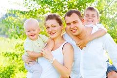 Familia joven alegre feliz en parque del verano Foto de archivo