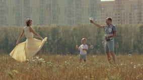 Familia joven amistosa de tres personas que disfrutan de día soleado Padre y sus burbujas que soplan del hijo feliz metrajes