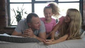 Familia joven atractiva con la hija en dormitorio almacen de video
