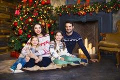 Familia joven cerca de la chimenea que celebra la Navidad Foto de archivo