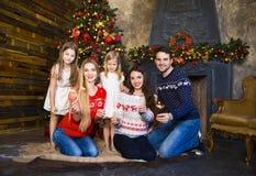 Familia joven cerca de la chimenea que celebra la Navidad Foto de archivo libre de regalías