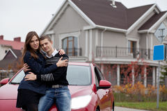 Familia joven cerca del coche rojo en casa del fondo Fotografía de archivo
