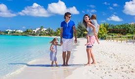 Familia joven con dos niños en la playa blanca tropical Imagen de archivo