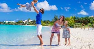 Familia joven con dos niños en la playa blanca tropical Fotografía de archivo libre de regalías